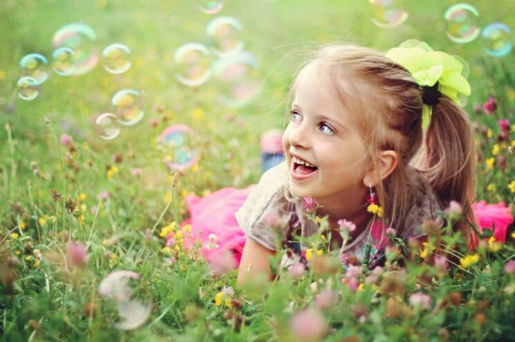 Sweet, happy, smiling six year old girl laying on a grass in a park playing with bubbles and laughing. 31 ways to get kids outside.