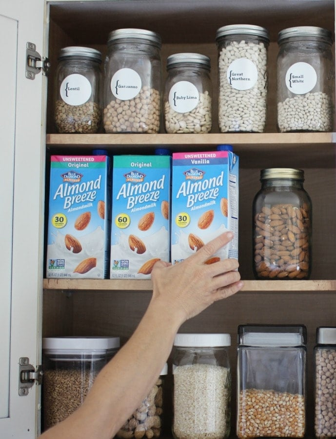 Reaching for shelf stable almond milk in a cupboard