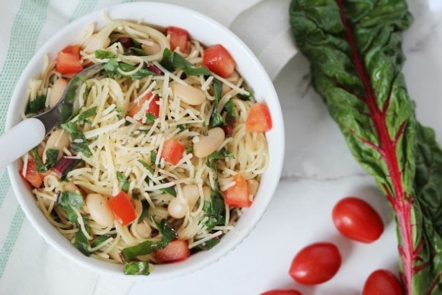 Garlic Pasta with Swiss Chard leaf next to bowl of pasta and 2 tomatoes