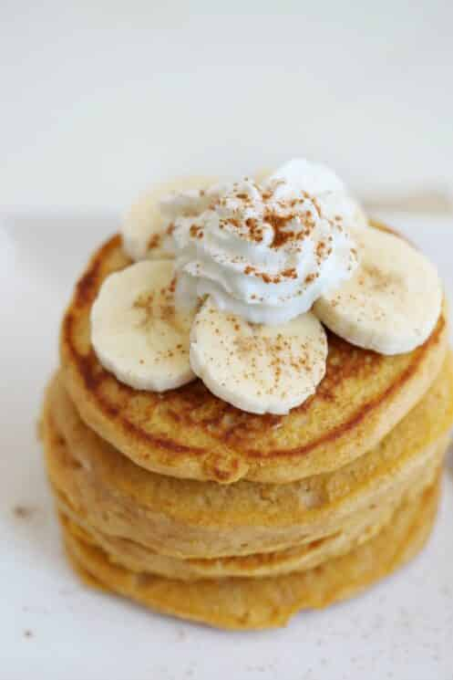 overhead view of a stack of sweet potato pancakes with banana slices and whip cream with cinnamon sprinkled
