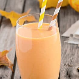 pumpkin smoothie in a glass with two festive straws