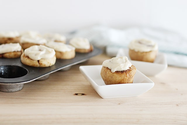 mini cinnamon rolls in a muffin tin with a single serving in a small white dish on a wooden table