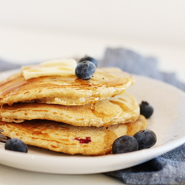 Pancakes with butter, blueberries and syrup on a white plate with a blue napkin