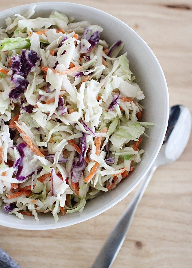 bowl of healthy coleslaw with serving spoon