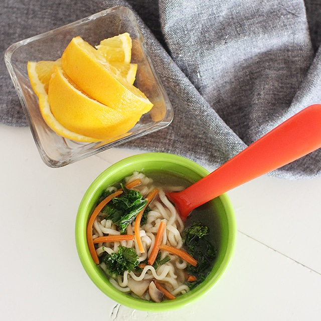green bowl of top ramen with veggies and orange slices