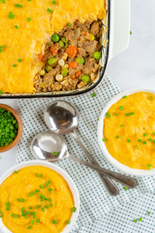 shepherds pie topped with mashed sweet potatoes in a baking dish with two smaller serving dishes and spoons