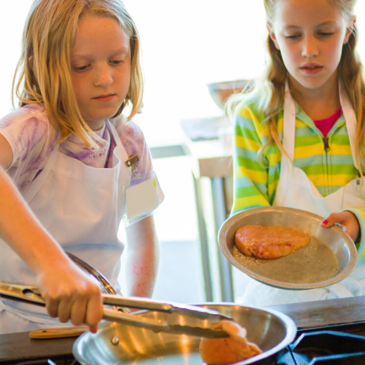 girls learning to cook chicken