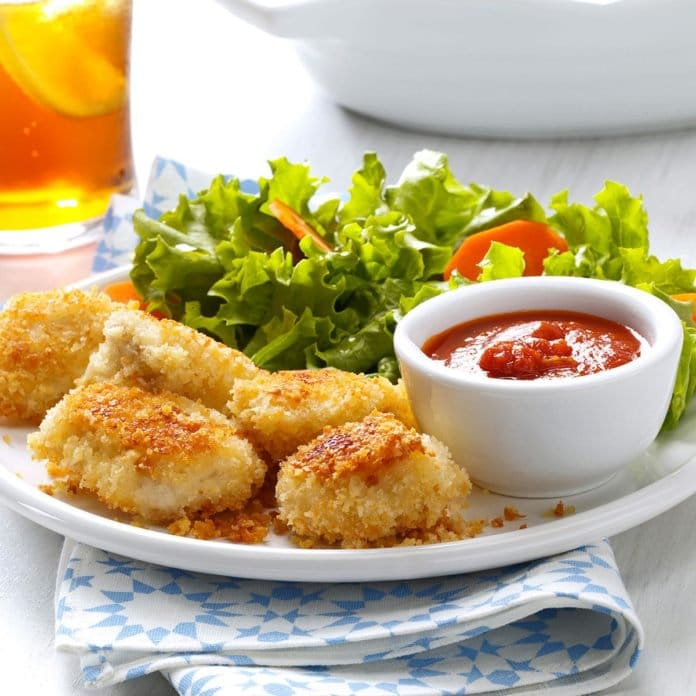 parmesan chicken nuggets on a plate with salad