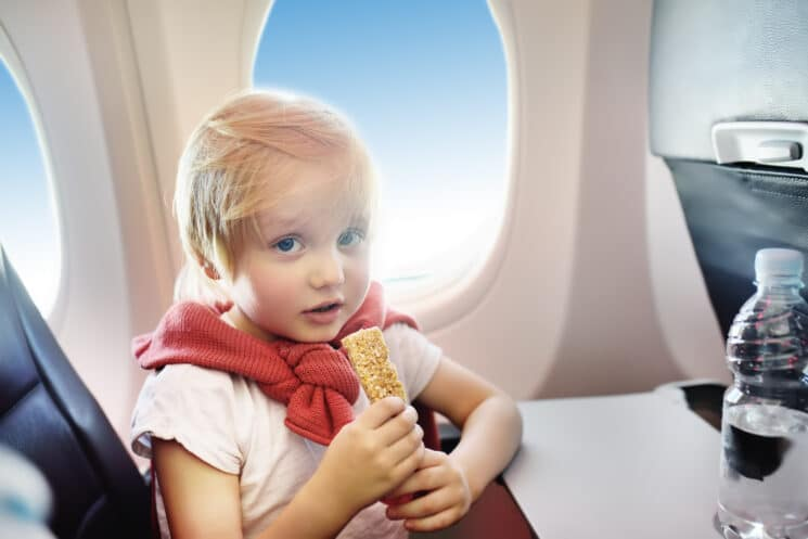 cute kid on a plane eating a healthy snack
