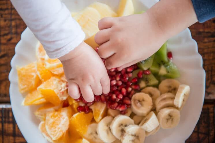 kids picking up fruit from a plate