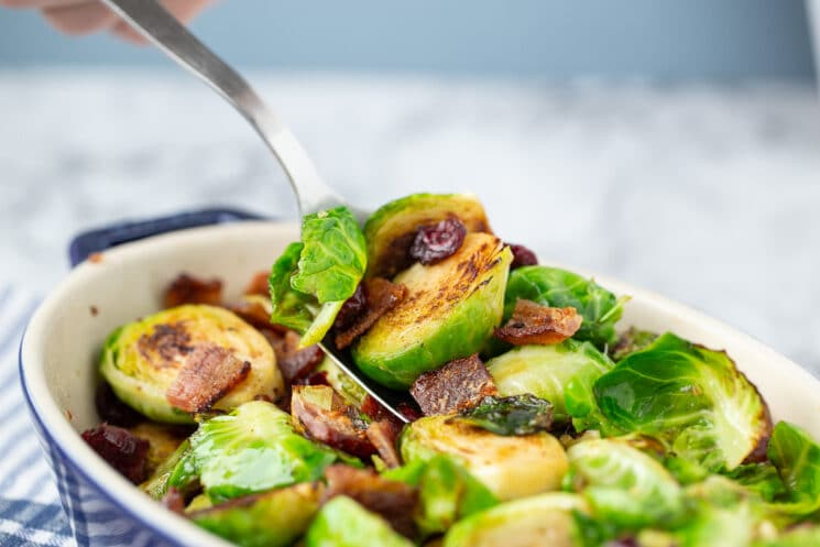 spoon scooping out brussels sprouts with bacon and cranberries