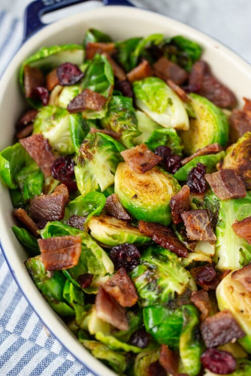 brussels sprouts with bacon and cranberries in a serving dish