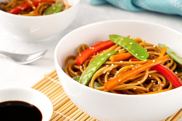 bowl of homemade veggie lo mein with a dish of soy sauce