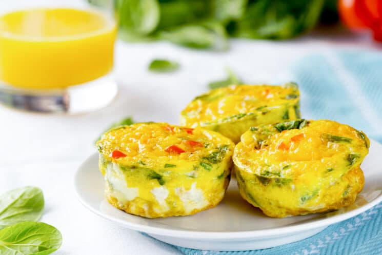 three breakfast egg muffins with veggies on a plate