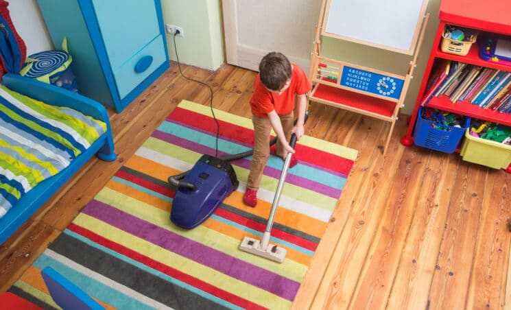 boy vacuuming his room summer chores