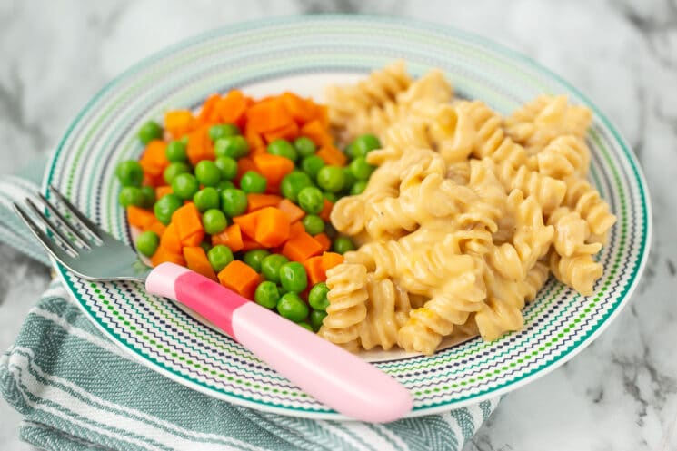 homemade mac and cheese with peas and carrots on a plate