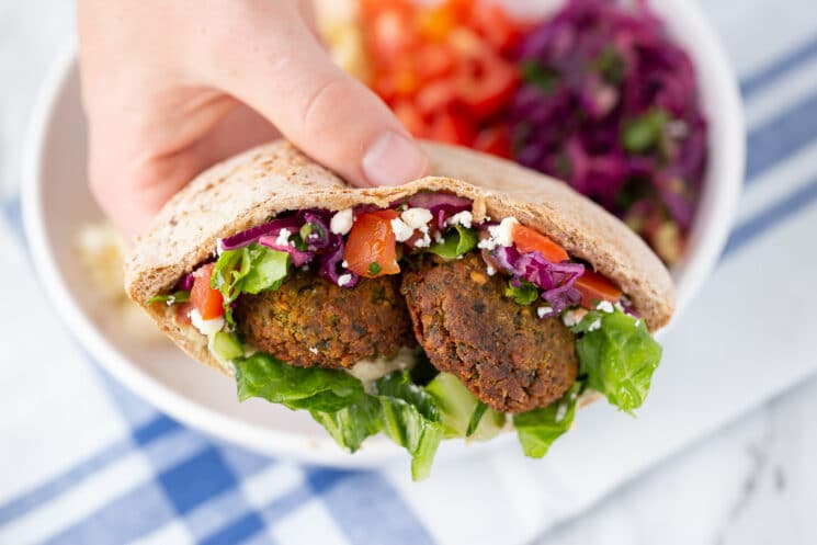 hand holding middle eastern pita pocket with falafel