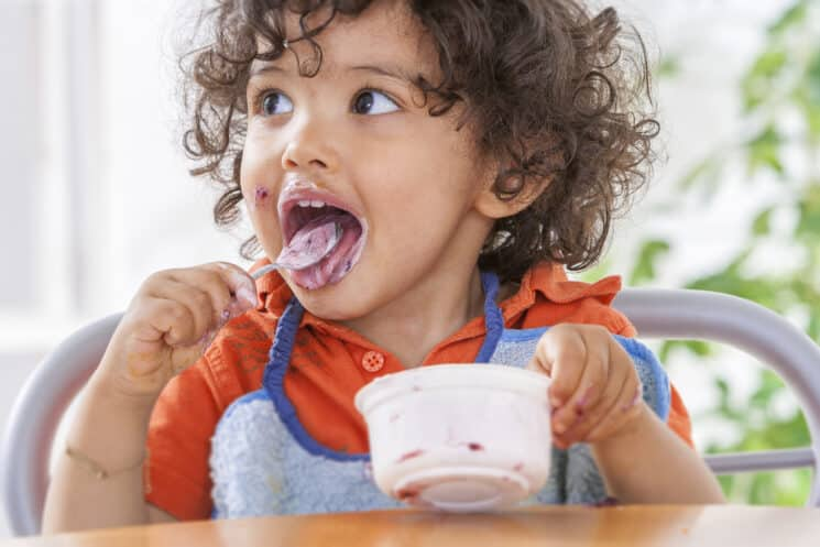 cute toddler eating yogurt with probiotics