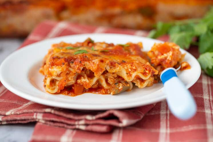 kids' plate of lasagna with a  blue fork