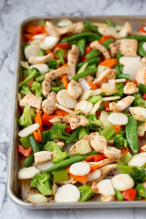 blanched veggies and cooked chicken freezing on a baking sheet