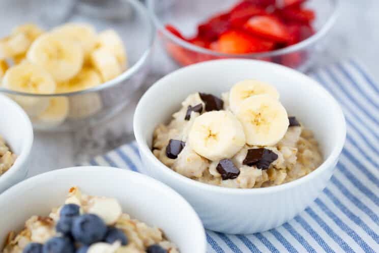 white bowls full of oatmeal with different toppings like bananas, chocolate chips, and blueberries