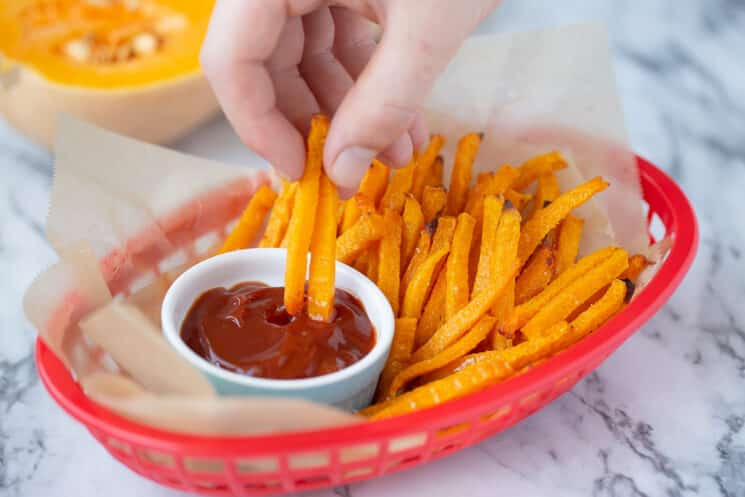 butternut squash fries dipping into ketchup