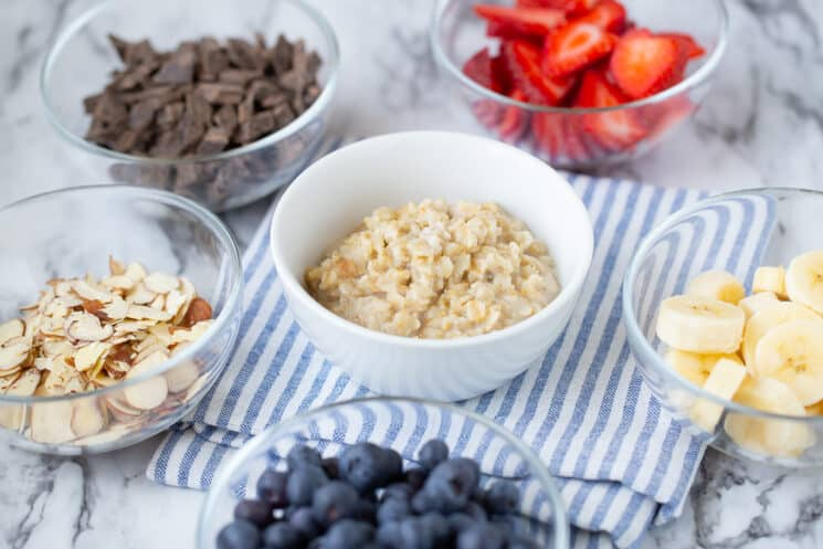 glass dishes full of many oatmeal topping ideas like strawberries, chocolate chunks, and slivered almonds