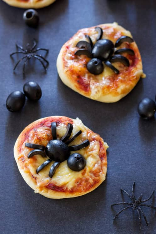 mini pita pizzas with black olive spiders on top