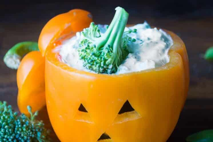 orange bell pepper carved like a jack-o-lantern and filled with ranch dip