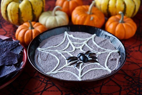 bowl of black bean hummus with a white spiderweb pattern