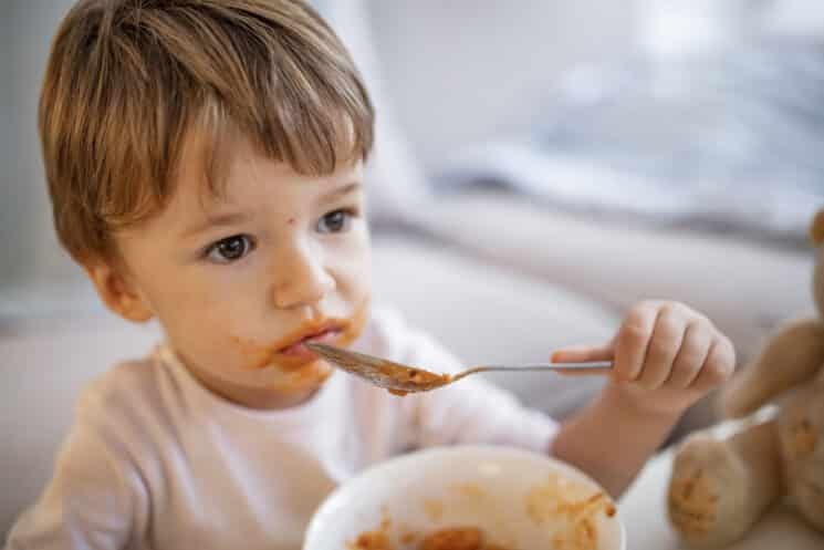 toddler boy eating from a bowl of pasta looks like he doesn't enjoy his meal