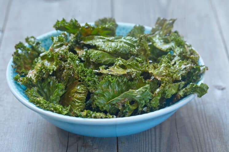 blue bowl full of kale chips on a wooden table