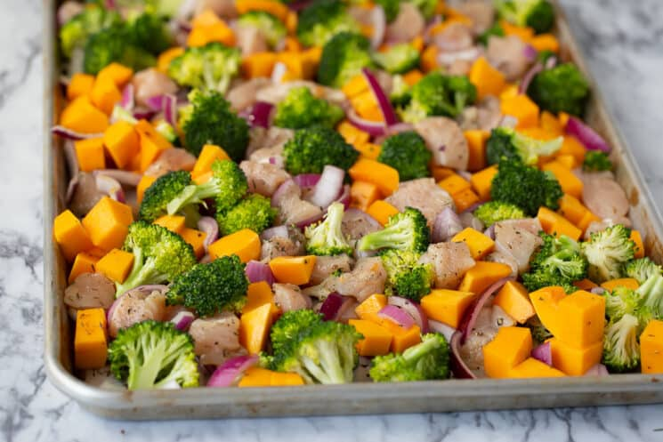 baking pan with raw ingredients like chicken, broccoli, onions, and squash