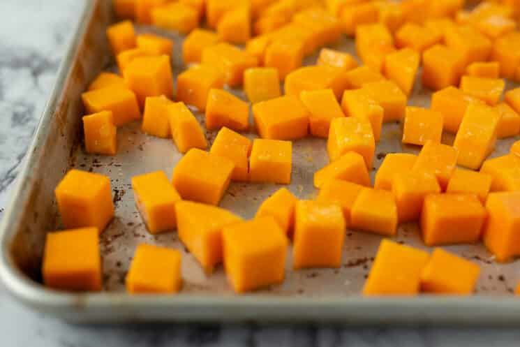 baking sheet with raw butternut squash cubes ready to go in the oven