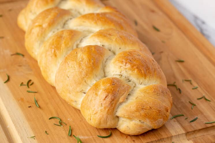 golden brown loaf of braided rosemary bread on a cutting board, sprinkled with rosemary leaves