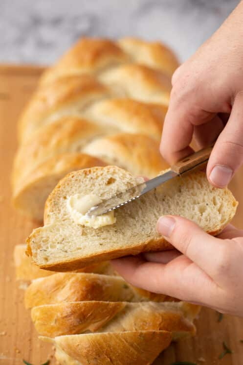 spreading butter on a slice of homemade braided bread