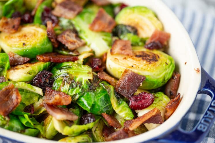 close up of cooked brussels sprouts in a dish sprinkled with crispy bacon and dried cranberries