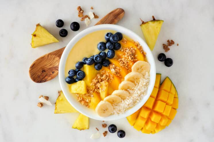 Mango smoothie bowl with blueberries, bananas, pineapple.