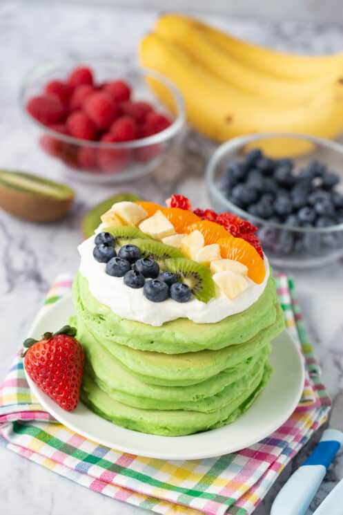 stack of spinach pancakes with whip cream and brightly colored berries on top