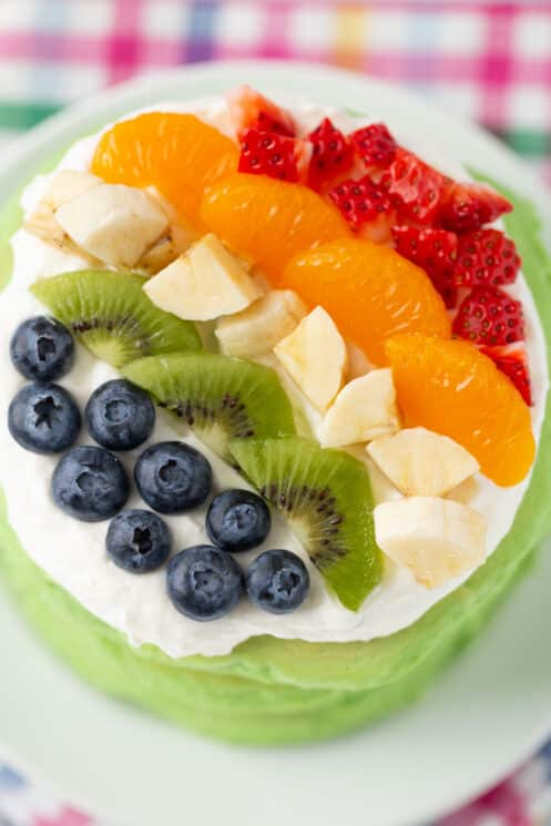 close up aerial view of stack of spinach pancakes with whip cream and brightly colored berries on top