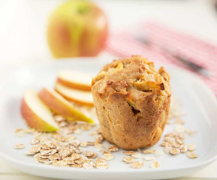 Apple Oat Muffin with apple slices in the background.