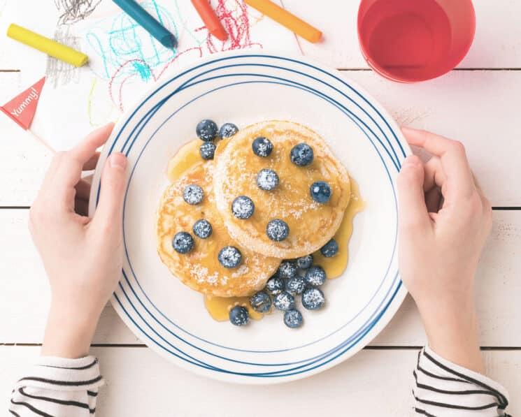 Blueberry Flaxseed Pancakes on a plate with childs hands