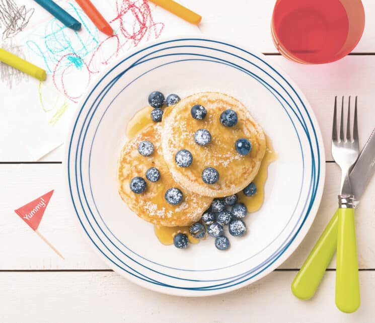 Blueberry Flaxseed Pancakes with kids art in the background
