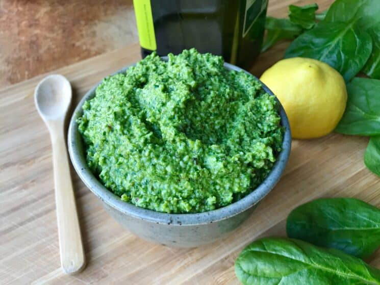 fresh spinach pesto in a bowl surrounded by ingredients