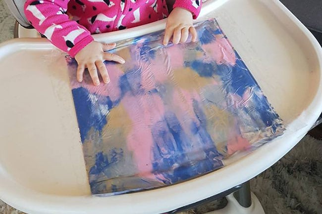 toddler using a plastic bag to smear paint on a high chair