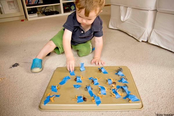 toddler taking apart toys taped to baking sheet for fine motor practice