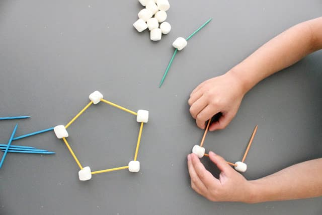 toddler building sculptures with toothpicks and marshmallows