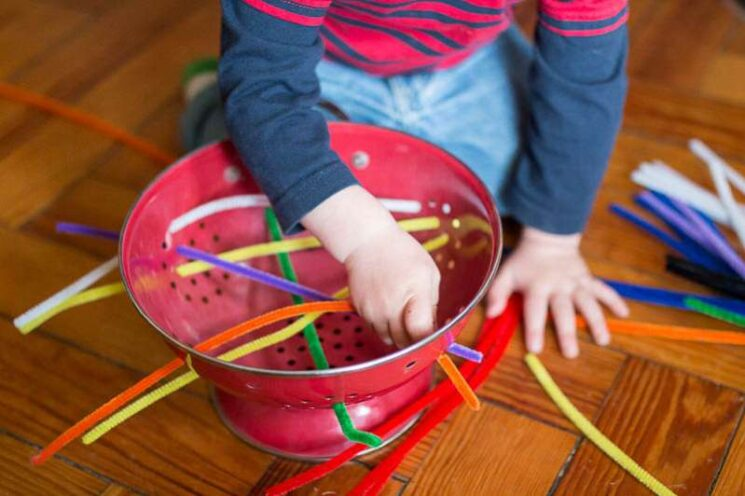 toddler threading pipe cleaners through a colander