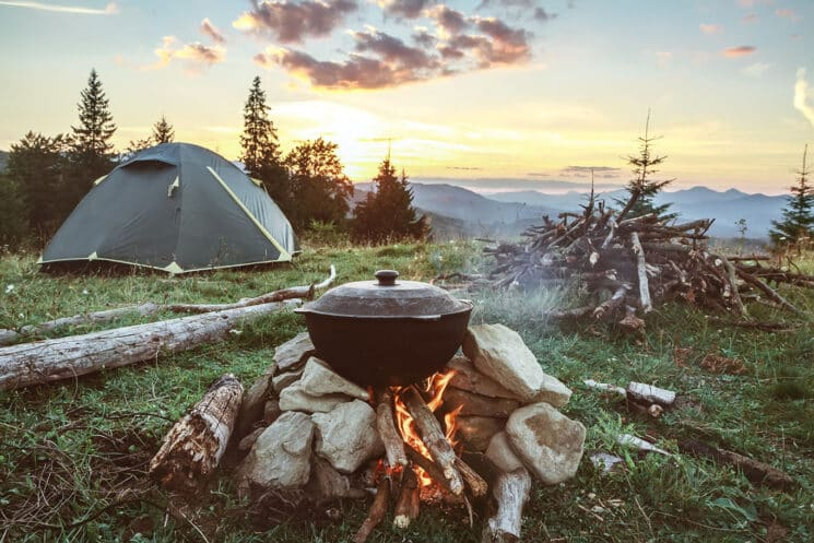 Camp Cooking scene with a Pot of food cooking over the fire with a tent in the background.