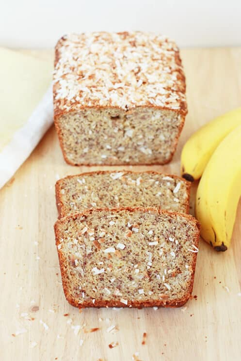 Coconut Banana Bread Sliced with Bananas next to the loaf